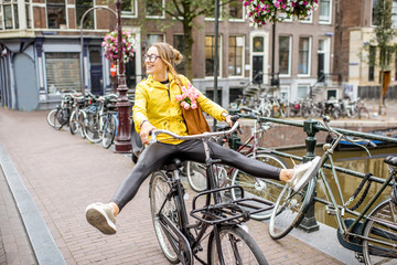 Young woman in yellow raincoat having fun riding a bicycle in Amsterdam city