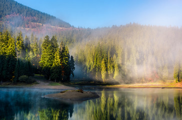 mountainous lake in foggy forest