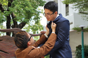 Two angry businessman is fighting in the outdoor park. Business conflict concept.