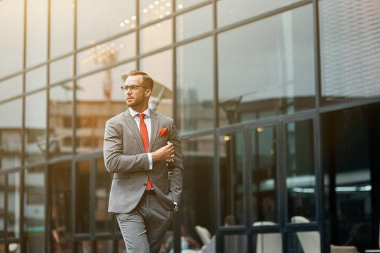 Professianal young businessman walking near modern building
