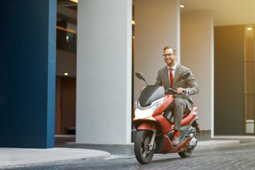 Aluminium Prints Scooter Positive young businessman riding a motorbike