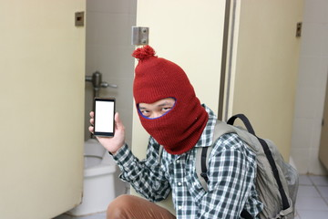 Masked burglar holding and showing mobile smart phone on his hands in toilet. Dangerous social crime concept.