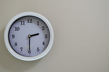 Time of the wall clock hung on a wall is 2:30.