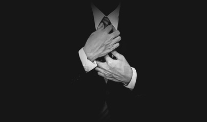 Businessman in black suit on black background, black and white