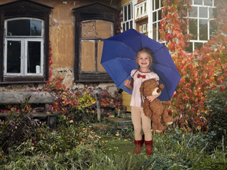 The child is under the blue umbrella with a toy bear. Farmland, farmhouse, garden. Autumn, red vines on the Windows of the house