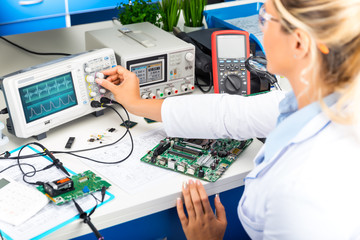 Female electronic engineer using oscilloscope in laboratory