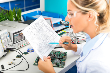 Female electronic engineer checking electronic circuit in laboratory