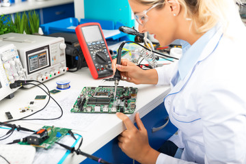 Young female electronic engineer soldering computer motherboard in laboratory