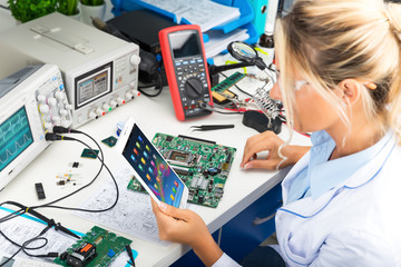 Female electronic engineer using tablet computer in laboratory