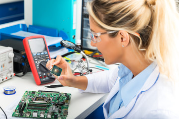 Female electronic engineer checking CPU microchip in laboratory