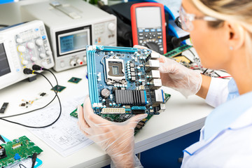 Female electronic engineer examining computer motherboard in laboratory