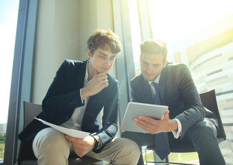 Mature businessman using a digital tablet to discuss information with a younger colleague in a modern business office.