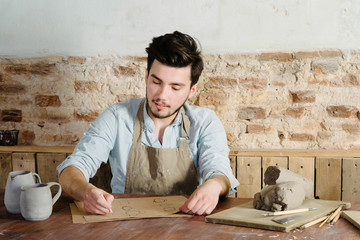 handsome young mexican potter does sketches of ceramics on the paper. concept of small business, handcrafted, hobby work.