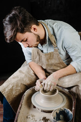 pottery, workshop, ceramics art concept - man working on potter's wheel with raw clay with hands, a male brunette sculpt a utensils near wooden table with tools, master in apron and a shirt