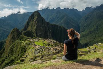 Frau blickt auf die Inka-Ruinen von Machu Picchu