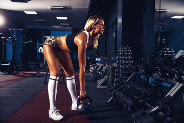 fitness blonde girl posing and exercising with dumbbell in gym