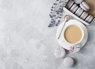 Macarons in box and on table with cup of coffee and lavender.
