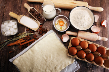 Bakery ingredients - flour, eggs, butter, sugar, yolk, almond nuts on blue table. Sweet pastry baking concept.