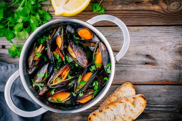 Canvas Prints Seafoods Delicious seafood mussels with with sauce and parsley. Lemon and baguette . Clams in the shells.