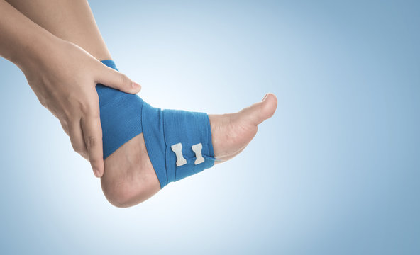 Ankle wrapped in elastic bandage on blue background,Ankle pain