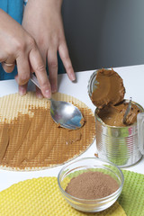 A woman is spreading condensed milk on a waffle cake. Waffle cake with boiled condensed milk and chocolate. Cooking process. Wafer cakes, cocoa and condensed milk are the ingredients for cooking.