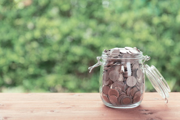 Money coins in glass jar on old  wooden table with green nature background