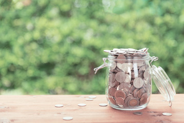 Money coins in glass jar on old  wooden table with green nature background,saving money concept