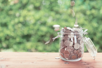 Money coins falling in glass jar on old  wooden table with green nature background,saving money concept