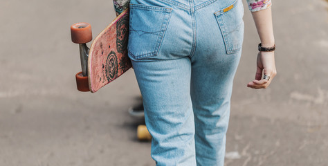 Back view of hipster girl wears jeans holding skateboard