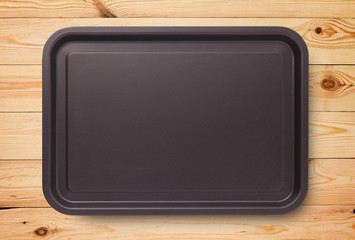 Empty baking tray for pizza on wooden table top view.