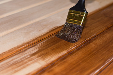 Painting a wooden surface with brushes and paint , copy space .
