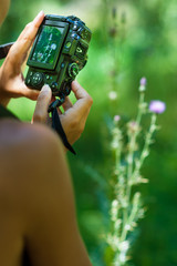 Detail of woman handhelding a camera photographing nature