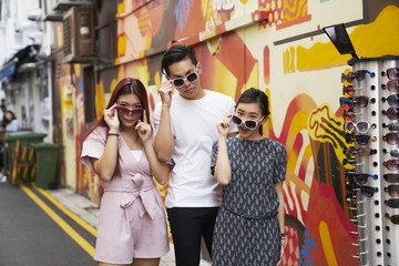 Three beautiful millennials with sunglasses exploring Haji Lane, Singapore