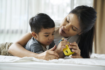Pretty Mother and son playing with toys on the bed