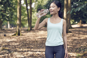 Woman hydrating after a workout at Botanic Gardens, Singapore