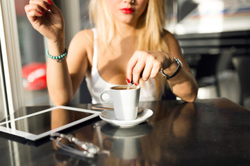 Beautiful young woman drinking coffee at a coffee shop.