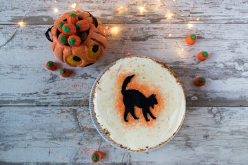 Halloween cake with black cat in rustic setting top view