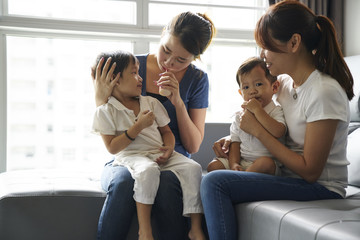 Affectionate young mothers bonding with their children in the living room