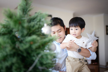 Man and his son decorating a Christmas tree