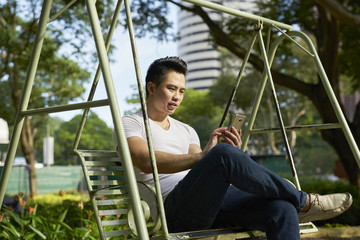 Man using his cellphone on a swing in Tanjong Pagar, Singapore