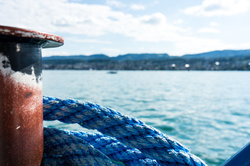 blue marine rope on ship with lake water and landscape