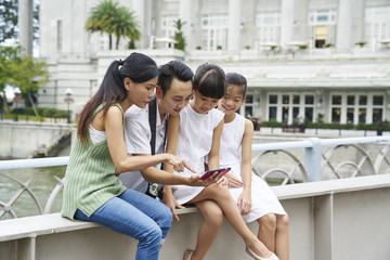 Family reviewing the images they took at Cavenagh Bridge, Singapore