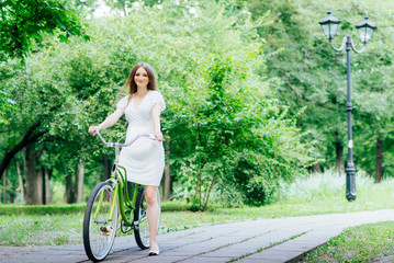 Pregnant girl in white dress rides a Bicycle on a background of hearts.