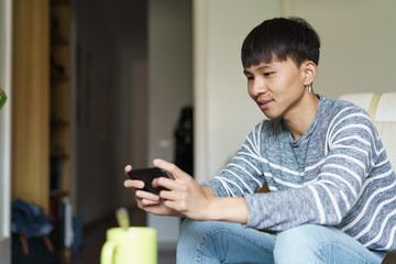Chinese man at home with his phone
