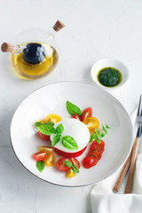 Caprese salad with ripe cherry tomatoes and mozzarella cheese with fresh basil leaves isolated on the white background. Top view.