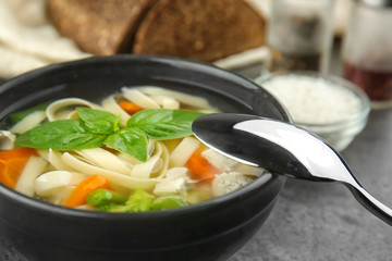 Bowl with delicious turkey soup on table, closeup