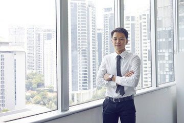 Portrait of a young Chinese banker with arms folded