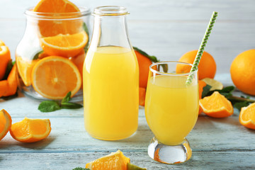 Bottle and glass with orange juice on wooden table