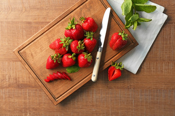 Fototapete - Cutting board with delicious fresh strawberry on wooden table