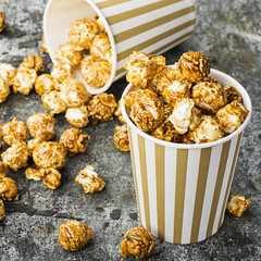 Appetizing homemade caramel popcorn in striped classic paper cups on a gray background. Selective focus.